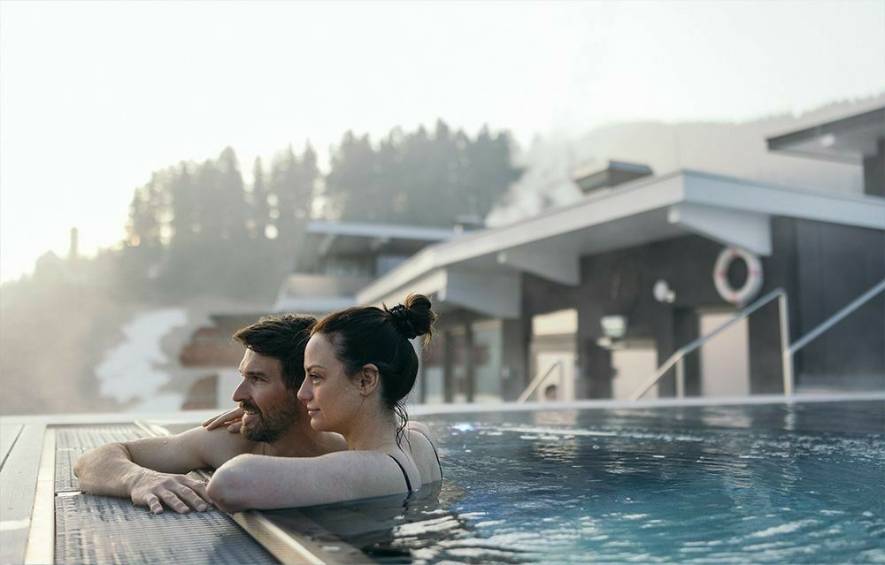 Woman in Infinity Sky Pool with view at the Wilder Kaiser