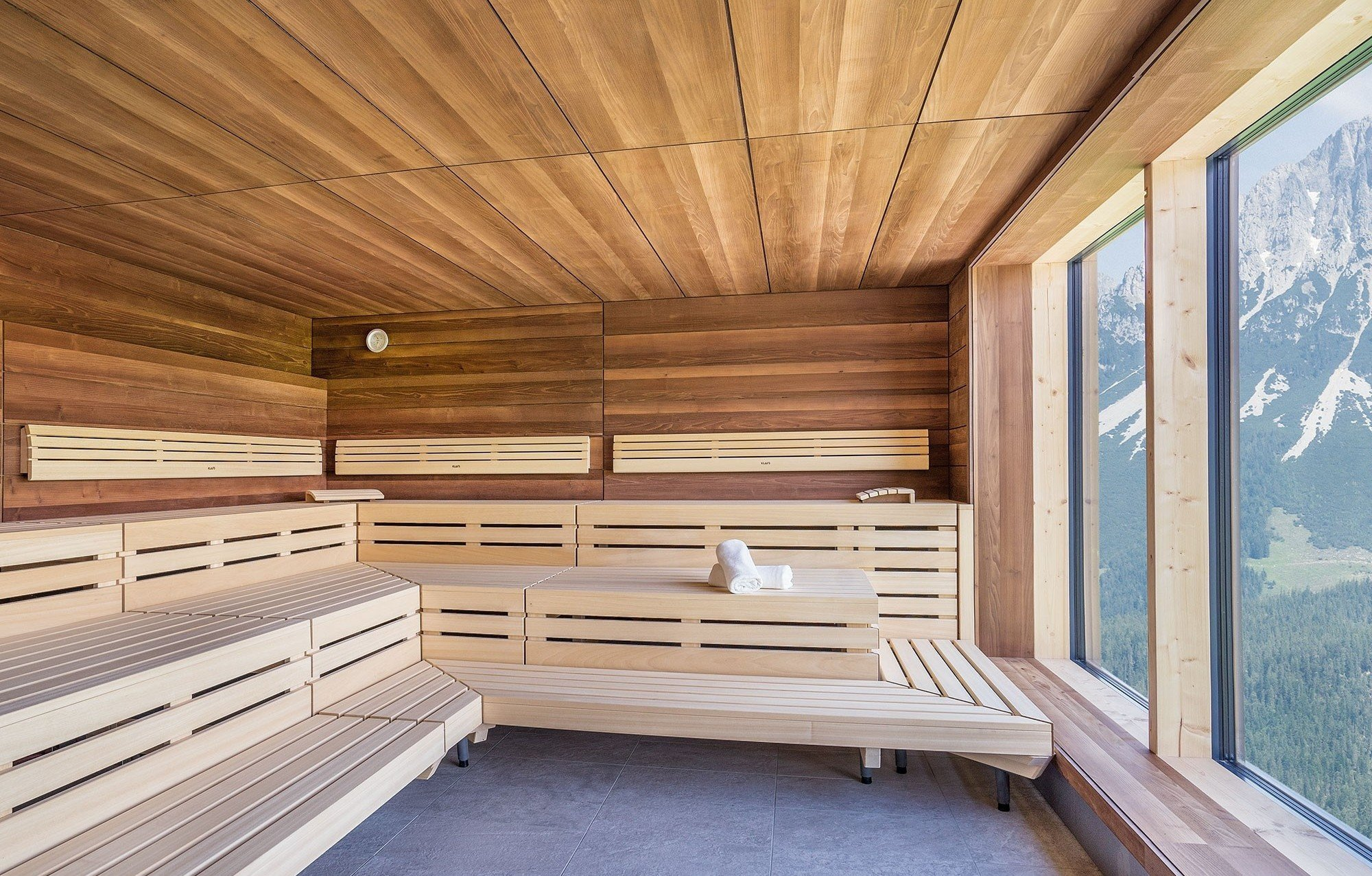 Sauna with towel at bank, panorma window with view on the mountains