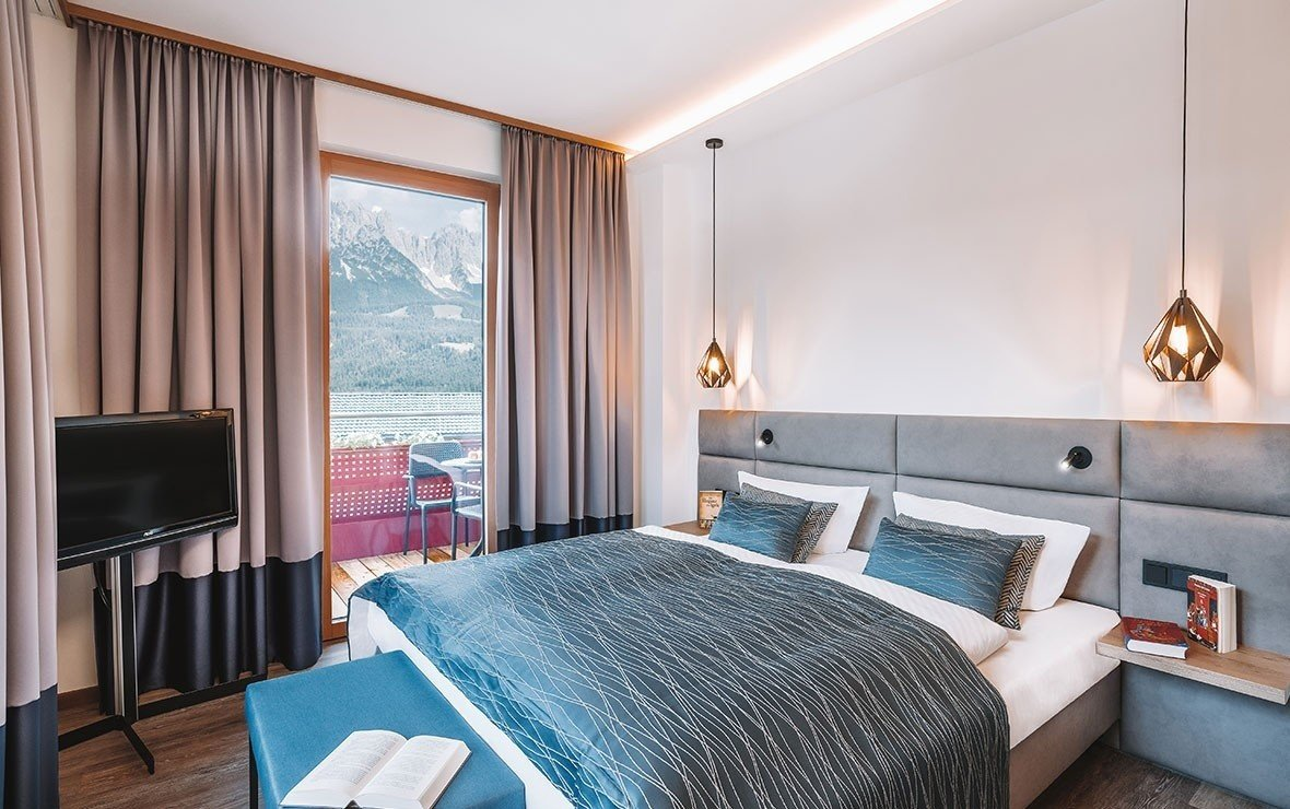 Room with double bed and balcony with view on the Wilder Kaiser